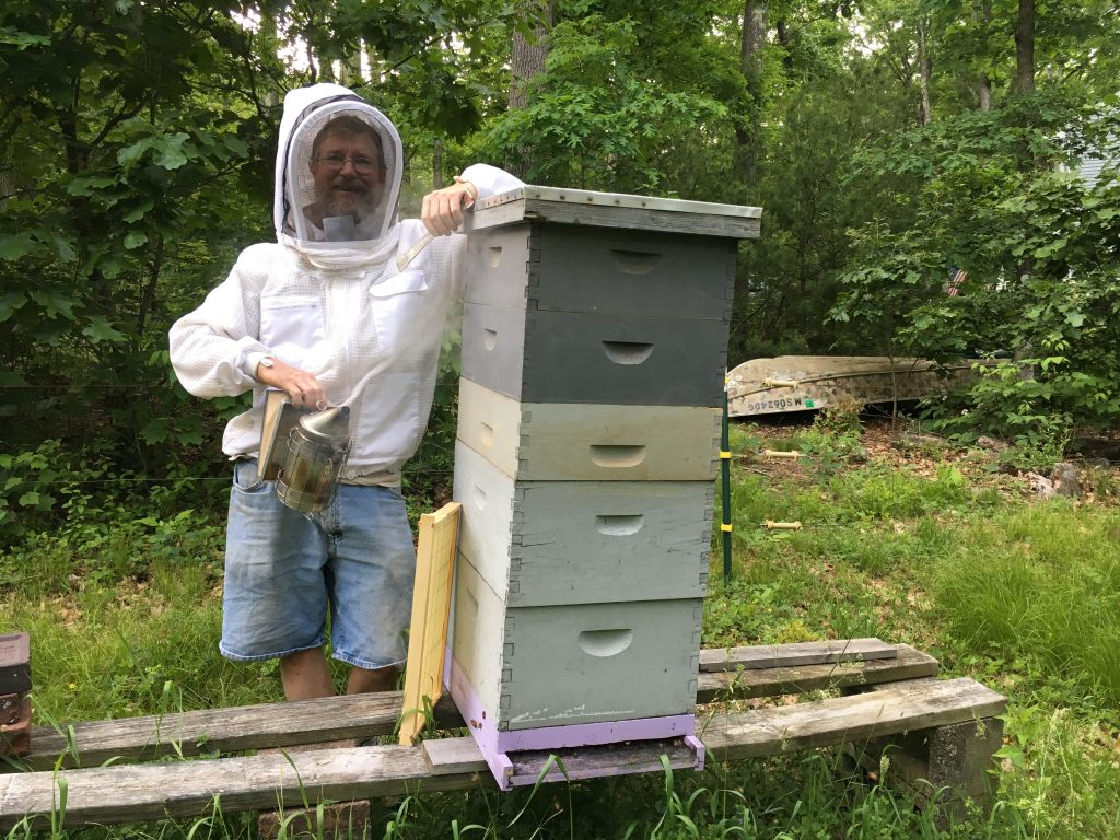 Donald Grimes stands by hive